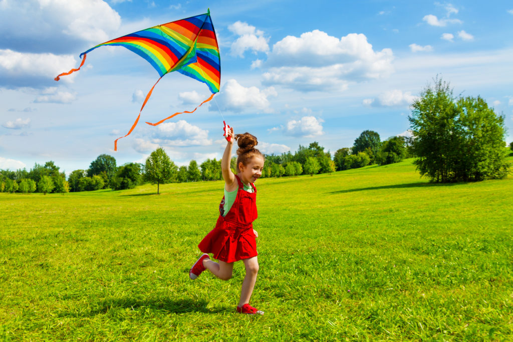Young girl flying kite as an after-school activity