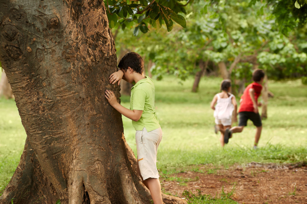 Young boys and girls playing hide and seek in park as an after school activity, with boy leaning on tree