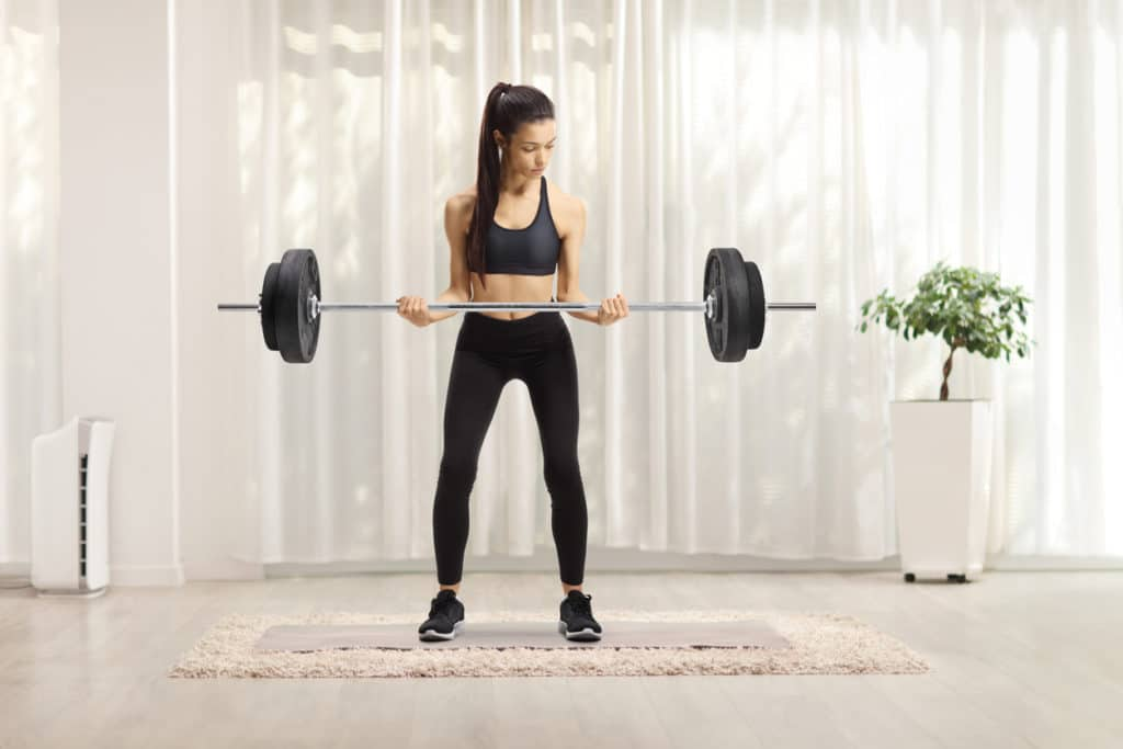Full length portrait of a young female in sportswear lifting weights at home