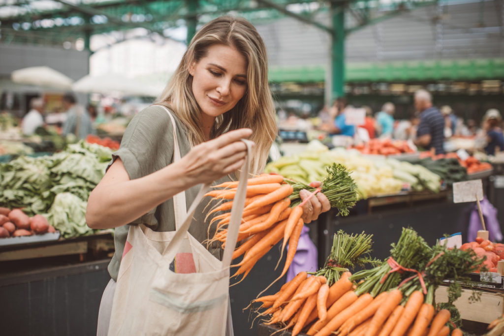 Woman with blond hair puts a bunch of carrots into her reusable tote bag.