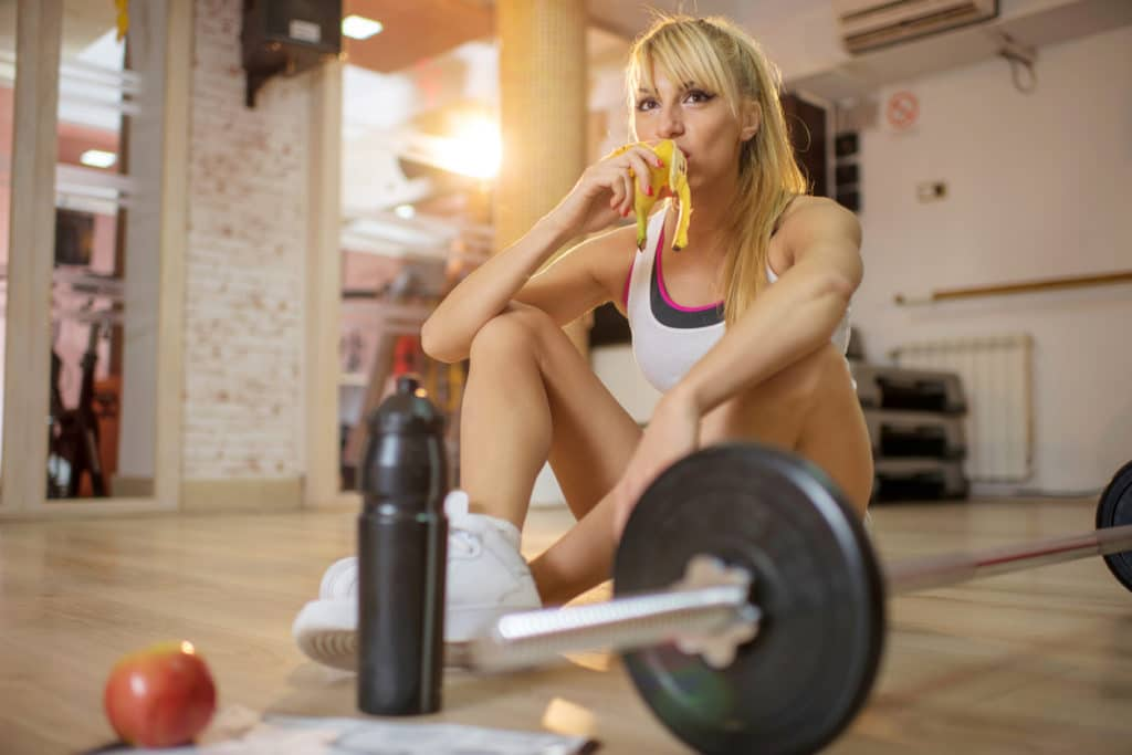 Woman sitting on floor in gym eating banana next to barbell with weights