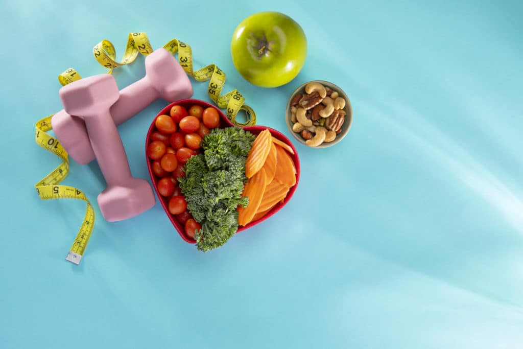 Vegetables in a heart bowl with dumbells and an apple on a blue background
