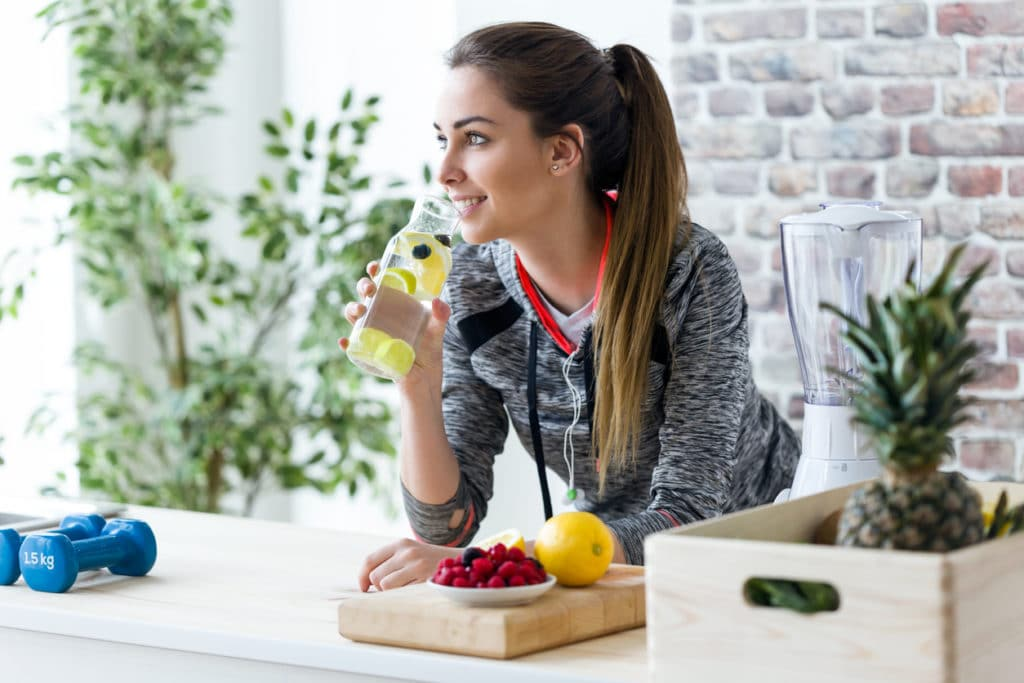 Sporty young woman looking sideways while drinking lemon juice in the kitchen at home.